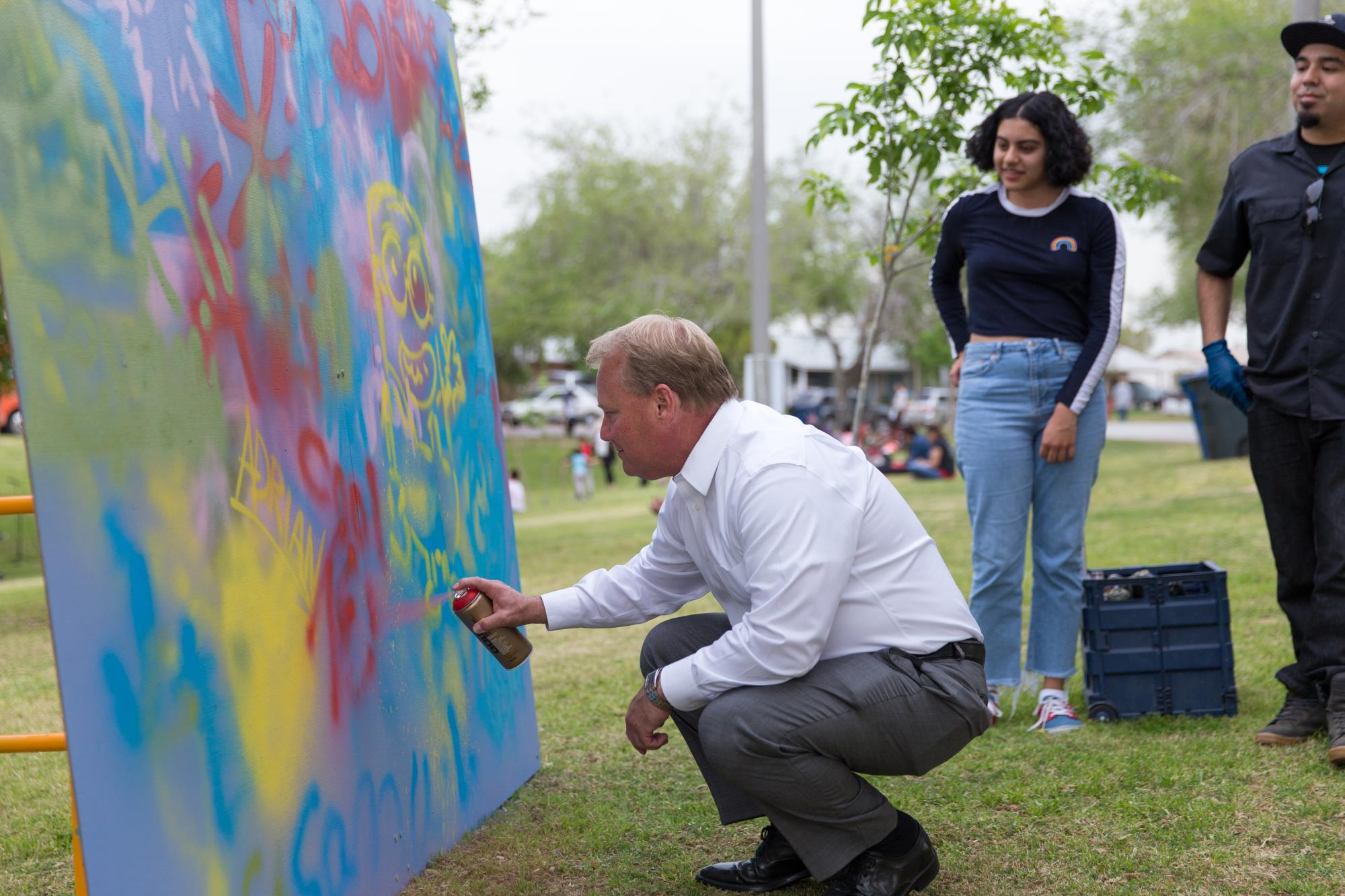 Mayor Mark Mitchell adds to a spray paint mural