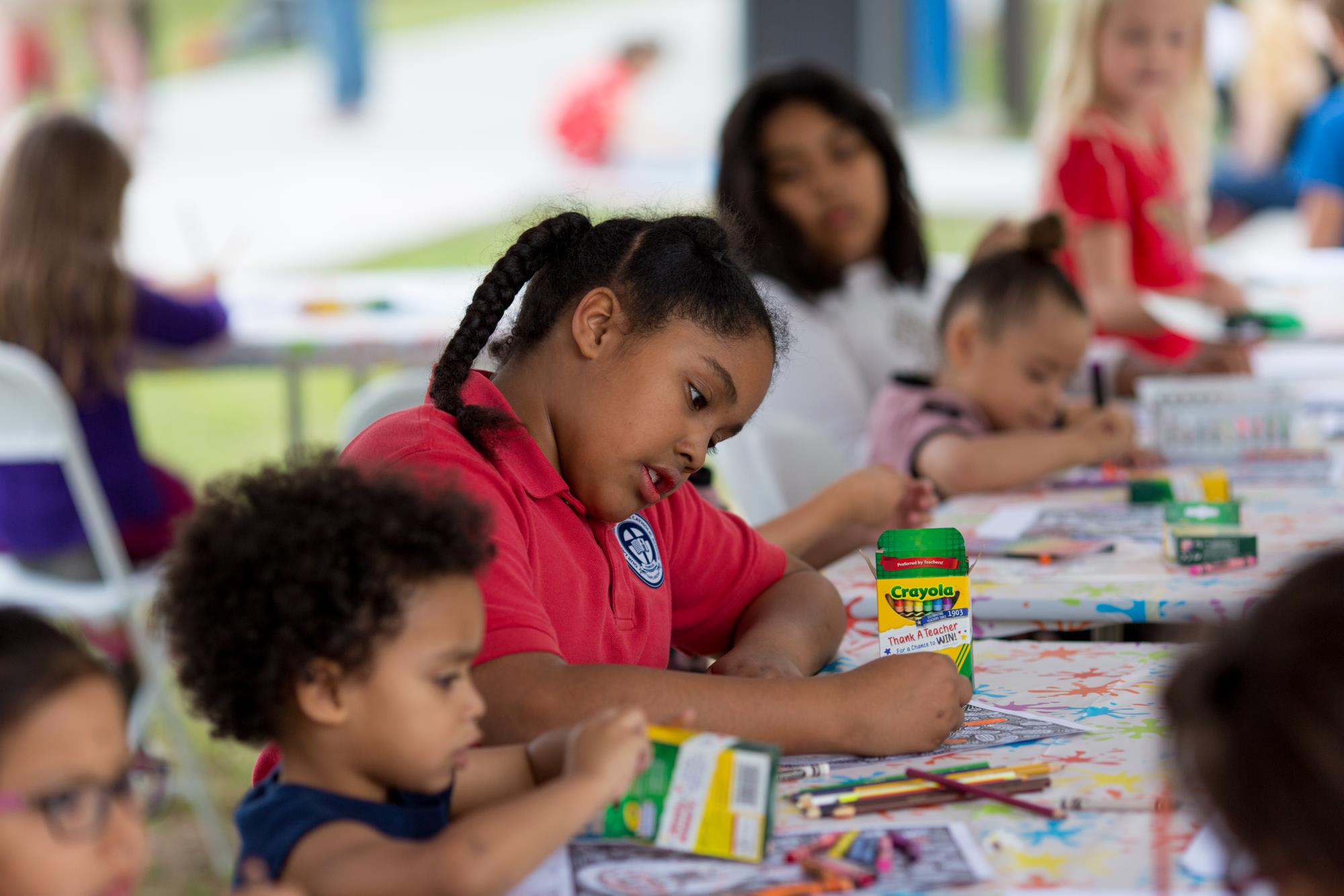 A group of children color at an art booth